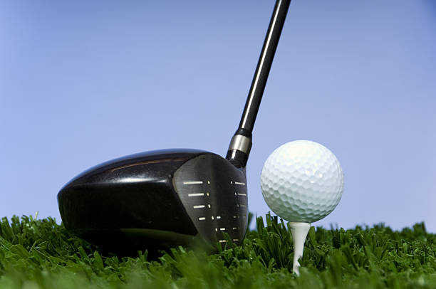 Golf club and ball on tee in front of blue sky background